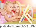 Mom helps a daughter to do homework 32248397