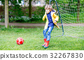 Active cute little kid boy playing soccer and 32267830