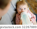 Father feeding newborn baby daughter with milk in 32267889