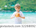Little kid boy drinking coconut juice on tropical 32268092