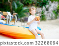 Little kid boy drinking coconut juice on tropical 32268094