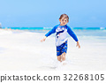 little blond kid boy having fun on tropical beach 32268105