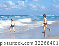 Two kid boys running on ocean beach in Florida 32268401