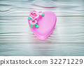 Heart-shaped present box on wood board 32271229
