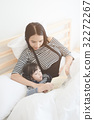 Mom reading a bed time story book to her daughter 32272267