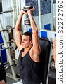 Man in gym workout with fitness equipment. 32272766