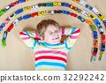Cute little blond kid boy playing with lots of toy 32292242