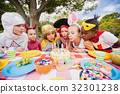 Cute children with fancy dress blowing on the candles together 32301238