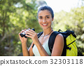 Woman smiling and holding binoculars 32303118