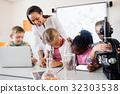 Smiling teacher helping pupils 32303538