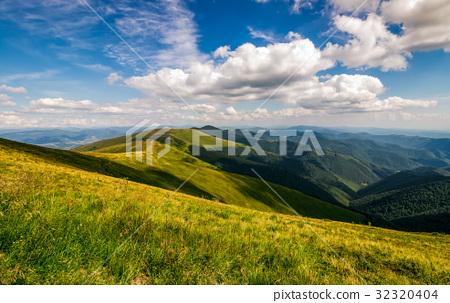 grassy meadow on hillside of mountain ridge 32320404