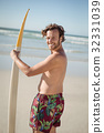 Portrait of happy shirtless man holding surfboard at beach 32331039