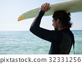 Surfer in wetsuit carrying surfboard over head at beach coast 32331256
