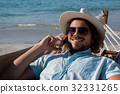 Man relaxing on hammock and talking on mobile phone on the beach 32331265