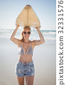 Portrait of young woman carrying surfboard at beach 32331576