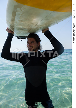 Surfer in wetsuit carrying surfboard over head at beach coast 32331683