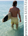 Surfer with surfboard looking at sea 32331721