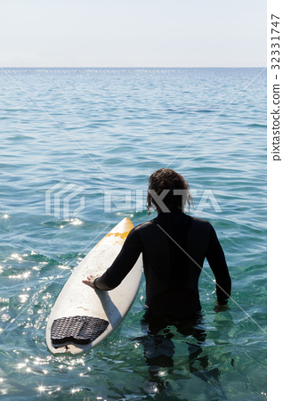 Surfer with surfboard standing in sea 32331747