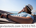Man relaxing on hammock and talking on mobile phone on the beach 32331765