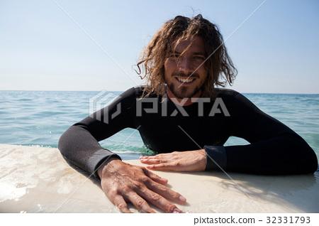 Surfer leaning on surfboard in sea 32331793