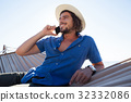 Man relaxing on hammock and talking on mobile phone on the beach 32332086