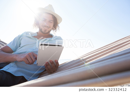 Man relaxing on hammock and using digital tablet on the beach 32332412