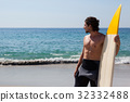 Surfer with surfboard standing at beach coast 32332488