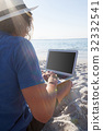 Man using laptop on the beach 32332541