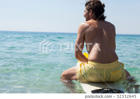Surfer sitting on surfboard at seacoast 32332645