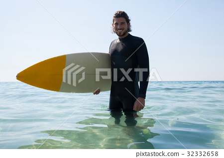 Surfer with surfboard standing at beach coast 32332658
