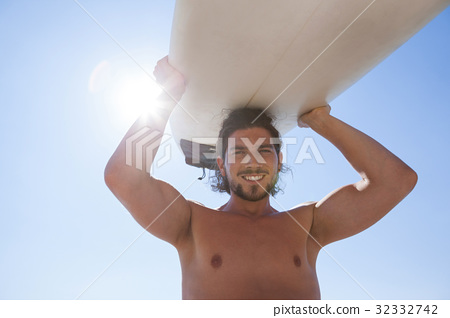 Surfer carrying surfboard over head against blue sky 32332742