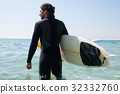 Surfer with surfboard looking at sea from the beach 32332760