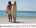 Surfer with surfboard looking at sea from the beach 32332790