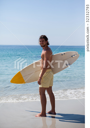 Smiling surfer with surfboard standing at beach coast 32332793