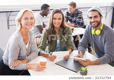 Portrait of smiling business people sitting at table 32332794