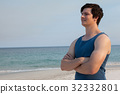 Man standing on beach with arms crossed 32332801