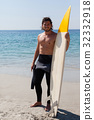 Smiling surfer with surfboard standing at beach coast 32332918