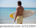 Surfer with surfboard looking at sea from the beach 32332964
