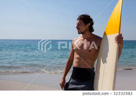 Surfer with surfboard standing at beach coast 32332982
