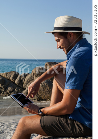 Man using digital tablet on the beach 32333105