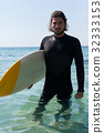 Surfer with surfboard standing at beach coast 32333153