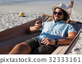 Man relaxing on hammock and using mobile phone on the beach 32333161
