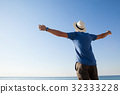 Man standing at beach with arms outstretched 32333228