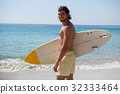 Smiling surfer with surfboard standing at beach coast 32333464