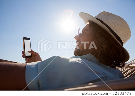Man relaxing on hammock and using mobile phone on the beach 32333478