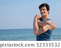 Smiling man stretching his hand on beach 32333532