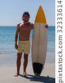 Smiling surfer with surfboard standing at beach coast 32333614