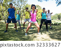 Group of people exercising in the park 32333627