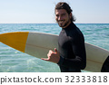 Surfer with surfboard standing at beach coast 32333818