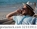 Man relaxing on hammock and talking on mobile phone on the beach 32333911